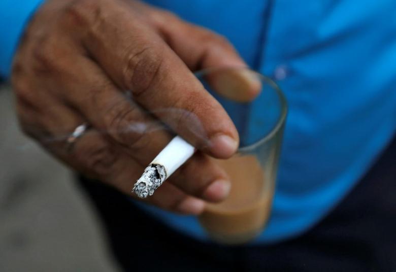 A man smokes a cigarette along a road in Mumbai, India, October 26, 2016. REUTERS/Danish Siddiqui/File Photo
