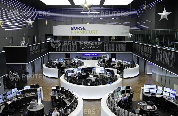 Traders work at their desks in front of the German share price index, DAX board, at the stock exchange in Frankfurt, Germany, November 29, 2016. REUTERS/Staff/Remote