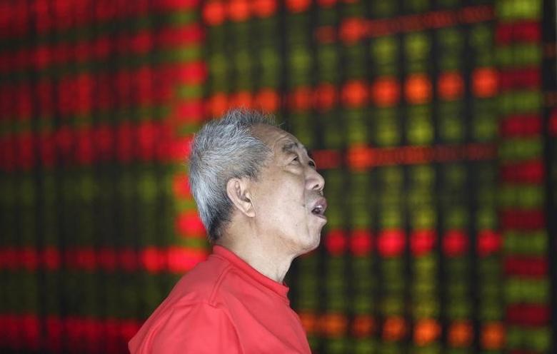 2013年8月16日,辽宁沈阳一家券商营业部内,一名股民在看大屏幕上的股票信息。REUTERS/Stringer