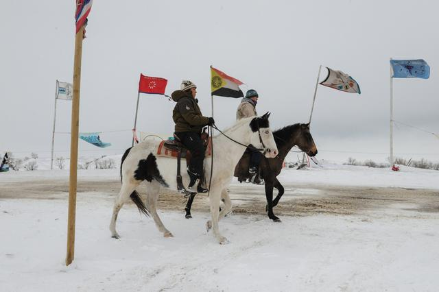 People ride horses in the Oceti Sakowin camp during a protest against plans to pass the Dakota Access pipeline near the Standing Rock Indian Reservation, near Cannon Ball, North Dakota, U.S. November 30, 2016. REUTERS/Stephanie Keith