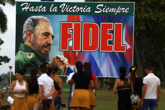 People stand in front of a billboard to Cuba's late President Fidel Castro in Santa Clara, Cuba, November 30, 2016. REUTERS/Ivan Alvarado