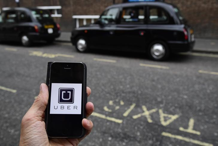 A photo illustration shows the Uber app logo displayed on a mobile telephone, as it is held up for a posed photograph in central London, Britain October 28, 2016. REUTERS/Toby Melville/Illustration - RTX2QV6X