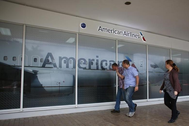People walk past an American Airlines office in Havana, Cuba, October 26, 2016. REUTERS/Alexandre Meneghini