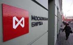 Женщина проходит мимо здания Московской биржи в российской столице 29 декабря 2014 года. Московская биржа зафиксировала в ноябре рост объемов торгов на денежном рынке на 75,7 процента, на рынке облигаций - на 43,6 процента, в сегменте акций - на 11,7 процента, валютой - на 8,4 процента, деривативами - на 6,5 процента. REUTERS/Sergei Karpukhin