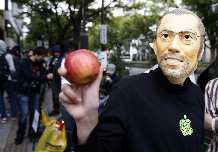 A man wearing a mask depicting Apple's co-founder Steve Jobs poses for a photograph with an apple as he waits for the release of Apple's new iPhone 6 and 6 Plus, in front of the Apple Store at Tokyo's Omotesando shopping district September 19, 2014. REUTERS/Yuya Shino/Files