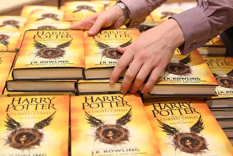 A store assistant holds copies of the book of the play of Harry Potter and the Cursed Child parts One and Two at a bookstore in London, Britain on July 31, 2016. REUTERS/Neil Hall/File Photo