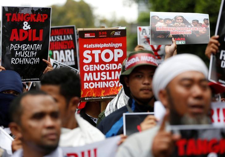 Protesters hold signs during a demonstration against what organisers say is the crackdown on ethnic Rohingya Muslims in Myanmar, outside the Myanmar embassy in Jakarta, Indonesia November 25, 2016. The text on the poster reads, ''Rohingya are our brothers''.    REUTERS/Darren Whiteside