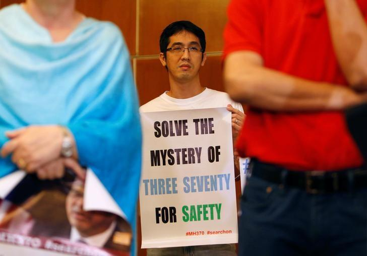 A family member of a passenger onboard the missing Malaysia Airlines flight MH370 holds a placard during a news conference following a meeting with Joint Agency Coordination Centre (JACC) in Kuala Lumpur, Malaysia July 21, 2016. REUTERS/Lai Seng Sin/Files