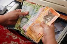 El presidente de Venezuela, Nicolás Maduro, dijo el viernes que su país imprimirá nuevos billetes de mayor denominación buscando facilitar el engorroso manejo de efectivo en la economía petrolera, afectada por una inflación de tres dígitos. En la foto de archivo, un cajero cuenta bolivares en una línea de cajas de un supermercado en Caracas el  20 de octubre de 2015. REUTERS/Carlos Garcia Rawlins
