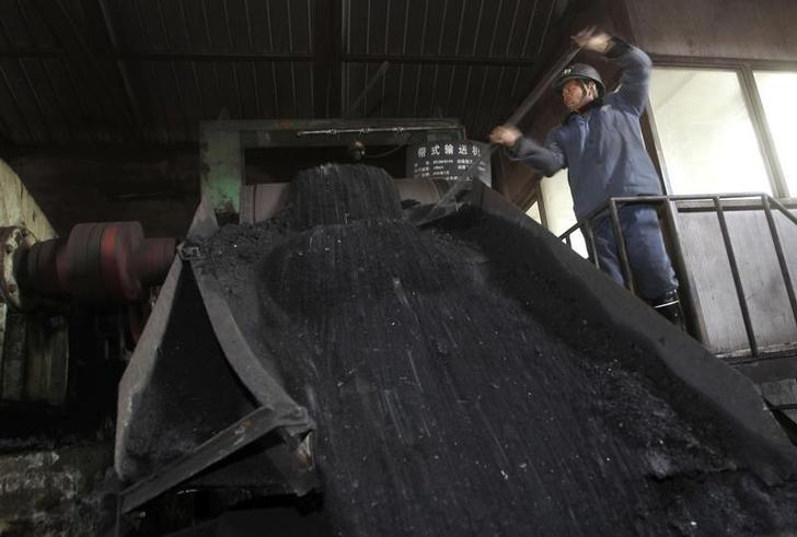 A worker shovels coal on a conveyor belt at a coal mine owned by Puda Coal Inc. in Pinglu, Shanxi province March 24, 2011. REUTERS/Stringer/Files