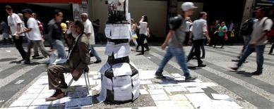 Una persona promocionando empleos en una calle en Sao Paulo, nov 19, 2014. El presidente de Brasil, Michel Temer, presentará el lunes los esperados detalles de una polémica propuesta de reforma al sistema de pensiones, en el centro de un plan de austeridad para sacar a la economía de Brasil de una profunda recesión.  REUTERS/Paulo Whitaker