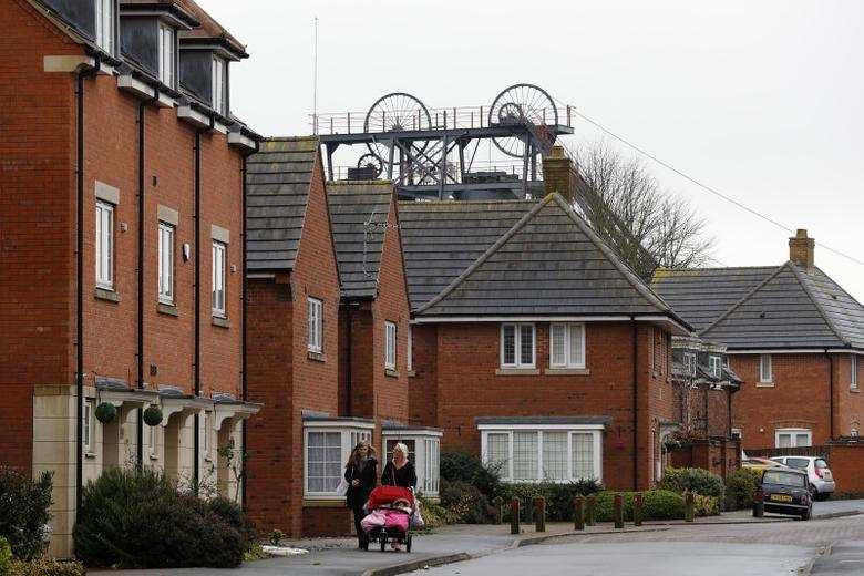 Women walk past new housing in the shadows of the former Snibston Colliery in Coalville, Britain November 23, 2016. REUTERS/Darren Staples