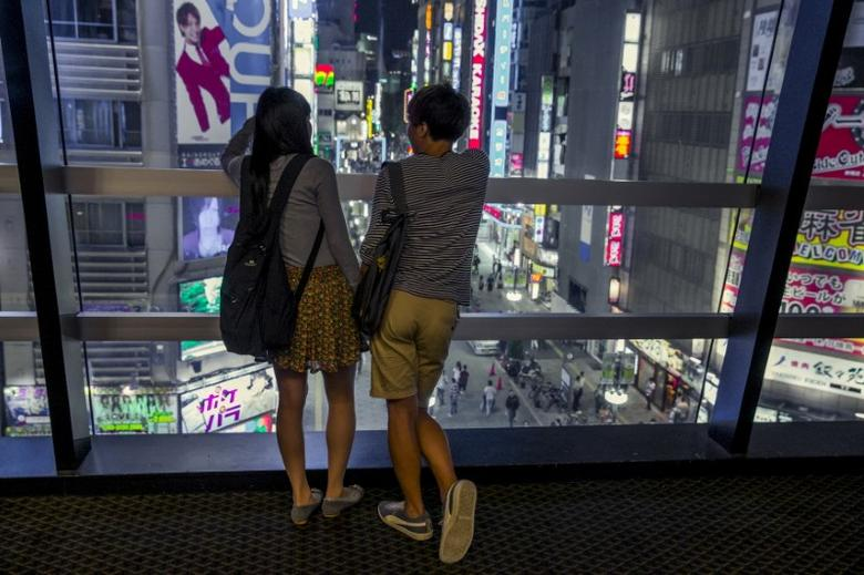 A couple overlooks Shinjuku's nightlife district of Kabukichoi in Tokyo, August 27, 2015.  REUTERS/Thomas Peter