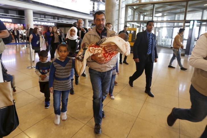Syrian refugee Ahmad al Aboud, and his family members, who will be resettled in the United States as part of a refugee admissions programme, walk to board their plane at the Queen Alia International Airport in Amman, Jordan, April 6,2016. REUTERS/Muhammad Hamed.