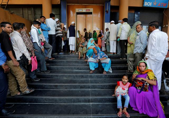 People wait for a bank to open to withdraw and deposit their money, after the scrapping of high denomination 500 and 1,000 Indian rupees currency notes, in Ahmedabad, India, December 5, 2016. REUTERS/Amit Dave/File photo