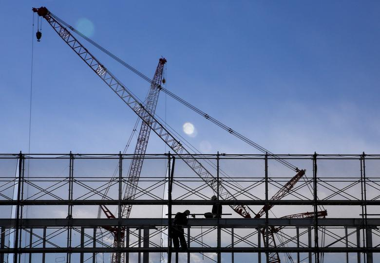 FILE PHOTO: Men work on a scaffolding as cranes are silhouetted against the sky at a construction site in Tokyo, Japan, February 17, 2016. REUTERS/Thomas Peter/File Photo