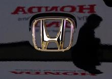 A visitor and the logo of Honda Motor Co are reflected on a Honda car at the company's headquarters in Tokyo January 30, 2009.      REUTERS/Toru Hanai/File Photo