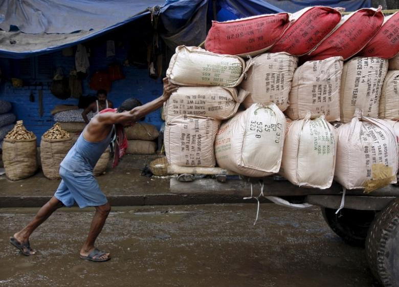 A labourer pushes a handcart loaded with sacks containing tea packets, towards a supply truck at a wholesale market in Kolkata, June 26, 2015. REUTERS/Rupak De Chowdhuri/Files