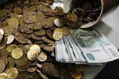 Рублевые купюры и монеты. Рубль существенно подорожал при открытии биржевых торгов понедельника в ответ на договоренность о сокращении добычи нефти между ОПЕК и не входящими в картель странами, что спровоцировало скачок нефтяных цен на 16-месячные максимумы.  REUTERS/Ilya Naymushin