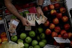 El billete de mayor denominación en Venezuela, el de 100 bolívares, saldrá de circulación en los próximos tres días, en una sorprendente medida para combatir el contrabando de papel moneda venezolano, anunció el domingo el presidente Nicolás Maduro. En la imagen, un cajero cuenta bolívares en un mercado del centro de Caracas, el 7 de diciembre de 2016. REUTERS/Ueslei Marcelino