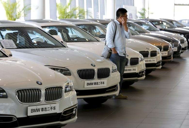 A man takes a look at second-hand BMW cars at a dealer shop in Beijing, China, September 11, 2015. REUTERS/Kim Kyung-Hoon