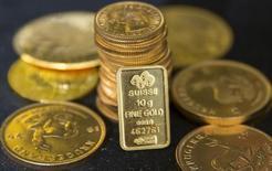 Золотые монеты и слиток в помещении дилера Hatton Garden Metals в Лондоне 21 июля 2015 года. Цены на золото опустилась до минимума более чем за 10 месяцев в понедельник на фоне ожиданий повышения процентных ставок ФРС на этой неделе, из-за которого растут курс доллара и доходность казначейских облигаций США. REUTERS/Neil Hall