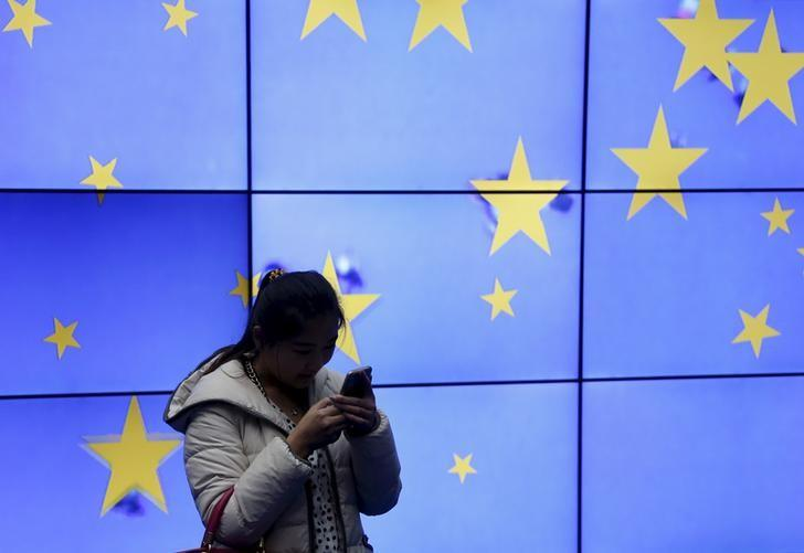 A visitor uses her mobile phone in front of an electronic board in the atrium of the European Council building in Brussels, Belgium, February 2, 2016.  REUTERS/Francois Lenoir/File Photo