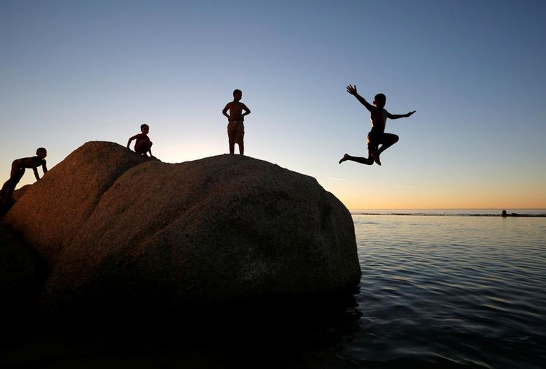 Children leap into a tidal pool at Camps Bay beach as temperatures soar in Cape Town, South Africa, December 11, 2016. REUTERS/Mike Hutchings