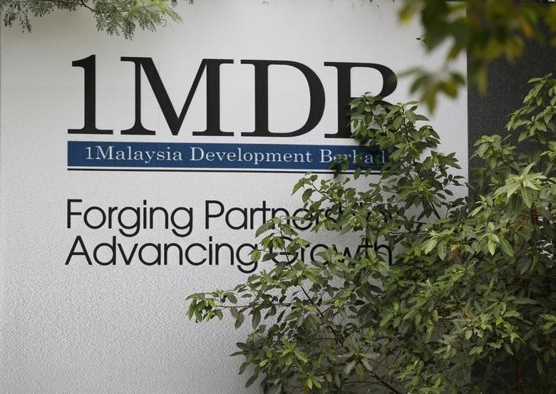 Foliage partly covers a 1 Malaysia Development Berhad (1MDB) billboard at the funds flagship Tun Razak Exchange development in Kuala Lumpur, Malaysia, July 3, 2015.  REUTERS/Olivia Harris
