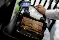 El presidente venezolano, Nicolás Maduro, ordenó el lunes el cierre temporal de la frontera con Colombia durante 72 horas, dentro de las medidas para contener el flujo de billetes de 100 bolívares, los de mayor denominación en Venezuela. En la imagen, una cajera con billetes en un restaurante de Caracas el 12 de diciembre de 2016. REUTERS/Ueslei Marcelino