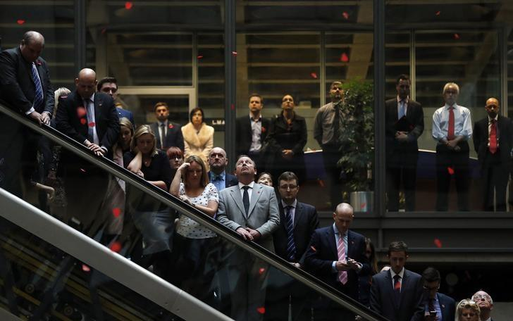 A Lloyd's of London staff member looks up at falling tissue paper poppies during their annual Remembrance Day service at the Lloyd's Building in the City of London November 11, 2014. REUTERS/Suzanne Plunkett/Files