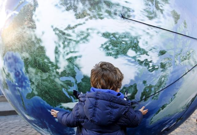 A child embraces a globe shaped balloon ahead of the start of the 2015 Paris World Climate Change Conference, known as the COP21 summit, in Rome, Italy , November 29, 2015. REUTERS/Alessandro Bianchi