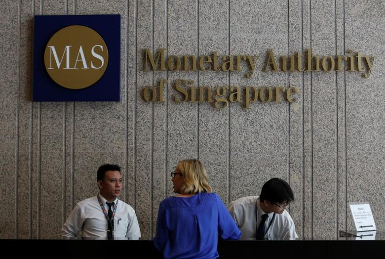A visitor speaks to security officers at the building of the Monetary Authority of Singapore (MAS) in Singapore February 21, 2013.  REUTERS/Edgar Su/Files