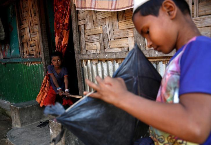 A Rohingya boy looks on as another boy makes a kite in Leda unregistered Rohingya Refugee Camp in Cox's Bazar, Bangladesh, November 22, 2016. REUTERS/Mohammad Ponir Hossain