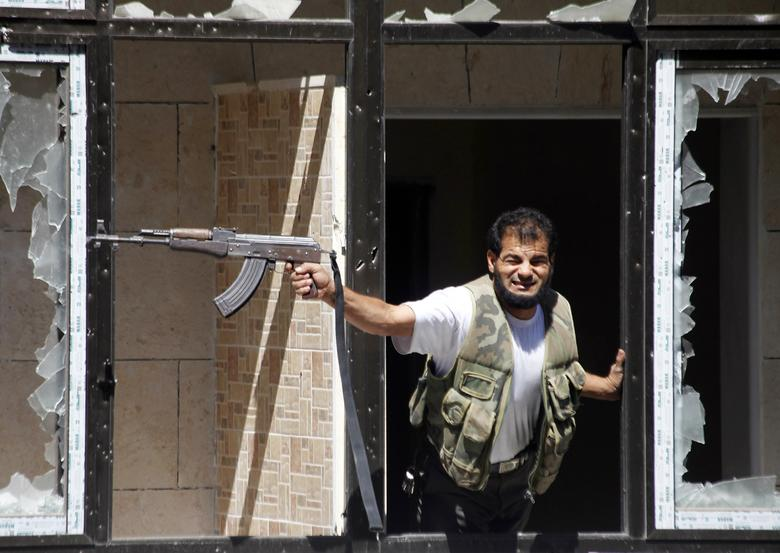 A Free Syrian Army fighter fires his weapon at the Justice Palace, which is controlled by forces loyal to Syria's President Bashar al-Assad, in Aleppo September 13, 2013. REUTERS/Hamid Khatib