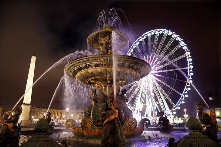 A giant Ferris wheel lights up the night sky for the Christmas holiday season behind a fountain and in front of the Louxor's Obelisque on the Place de la Concorde square in Paris, France, December 11, 2016.   REUTERS/Charles Platiau