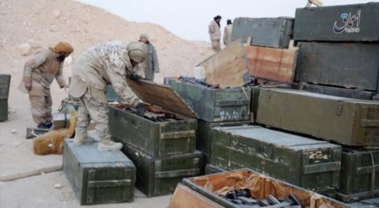 Islamic State fighters search weapon boxes in a Russian base in what is said to be Palmyra, Syria in this still image taken from video uploaded to social media on December 13, 2016.  Amaq News Agency/Handout via Reuters TV