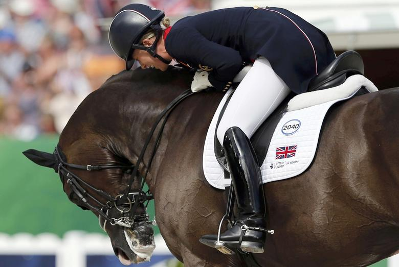 British rider Charlotte Dujardin celebrates with her horse Valegro during Individual freestyle Competition Dressage at the World Equestrian Games at the d'Ornano stadium in Caen, August 29, 2014. REUTERS/Regis Duvignau/File Photo