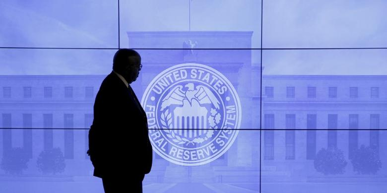 A security guard walks in front of an image of the Federal Reserve in Washington, DC, U.S., March 16, 2016. REUTERS/Kevin Lamarque/File Photo