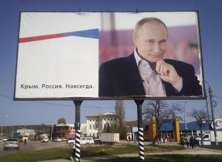 A billboard with a portrait of Russian President Vladimir Putin is displayed on a street in Kerch, Crimea, April 7, 2016.  The board reads:
