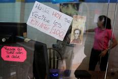 """El presidente de Venezuela, Nicolás Maduro, exhibió el jueves ejemplares de los billetes y monedas que estrenará el país y dijo que las nuevas denominaciones están listas para circular, aún cuando los venezolanos cargados de billetes de 100 bolívares, ya casi fuera de circulación, se quedaron esperando. en la imagen, un billete de 100 bolívares junto a un cartel que dice """"Hasta hoy se recibe los billetes de 100"""", en una tienda del barrio de Petare, en Caracas, Venezuela, el 12 de diciembre de 2016. REUTERS/Marco Bello"""