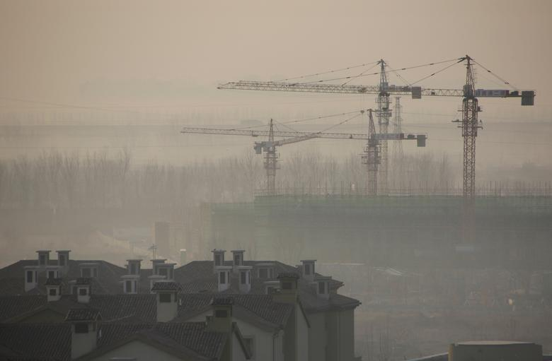 Apartment blocks are pictured next to a construction site on a hazy day in Wuqing district of Tianjin, China, December 10, 2016. REUTERS/Jason Lee