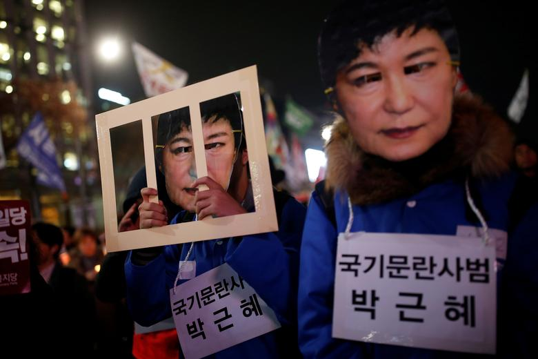 People march during a protest calling for South Korean President Park Geun-hye to step down in central Seoul, South Korea, November 30, 2016. The signs read ''Offender disturbing order of nation, Park Geun-hye''.  REUTERS/Kim Hong-Ji/Files