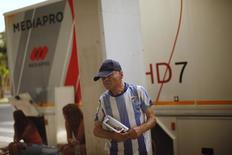 En la imagen, un aficionado del Málaga escucha la radio cerca de un autobús de Mediapro antes de un partido amistoso entre el Málaga y el Everton en el exterior del estadio de La Rosaleda, Málaga, 11 de agosto de 2012. Grupos de inversores asiáticos, europeos y estadounidenses presentaron esta semana alrededor de 10 ofertas no vinculantes para tomar una participación en el grupo español de gestión de derechos audiovisuales Imagina, dijeron el viernes dos fuentes conocedoras de la operación.REUTERS/Jon Nazca