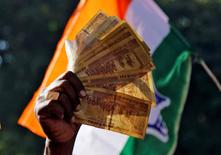 A man displays 500 Indian rupee notes during a rally organised by India's main opposition Congress party against the government's decision to withdraw 500 and 1000 Indian rupee banknotes from circulation, in Ajmer, India, November 24, 2016. REUTERS/Himanshu Sharma/File Photo