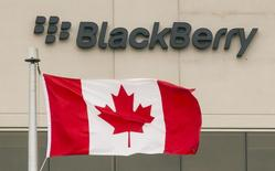 A Blackberry logo hangs behind a Canadian flag at their offices on the day of their annual general meeting for shareholders in Waterloo, Canada June 23, 2015.  REUTERS/Mark Blinch/File Photo