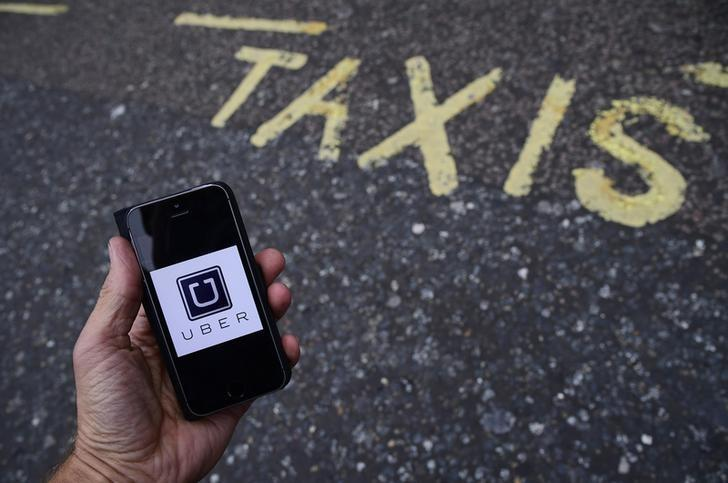 A photo illustration shows the Uber app logo displayed on a mobile telephone, as it is held up for a posed photograph in central London, Britain October 28, 2016. REUTERS/Toby Melville/Illustration/File Photo