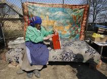 Пожилая женщина бросает бюллетень в избирательный ящик в молдавской деревне Дорочая. 5 апреля 2009 года. Молдавия, где женщины выходят на пенсию в 57, а мужчины - в 62 года, решила постепенно - в течение 3-12 лет - поднять планку до 63 лет. REUTERS/ Gleb Garanich