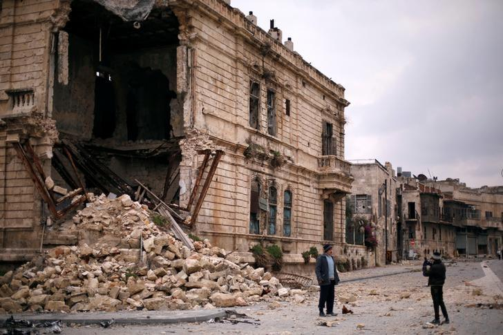 People take pictures in front of the old Customs building in the government controlled Old City of Aleppo, Syria December 17, 2016. REUTERS/Omar Sanadiki