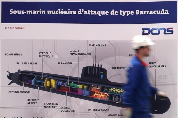 An employee walks past a poster showing a Barracuda submarine at the industrial site of the naval defence company and shipbuilder DCNS in La Montagne near Nantes, France, April 26, 2016. REUTERS/Stephane Mahe/Files